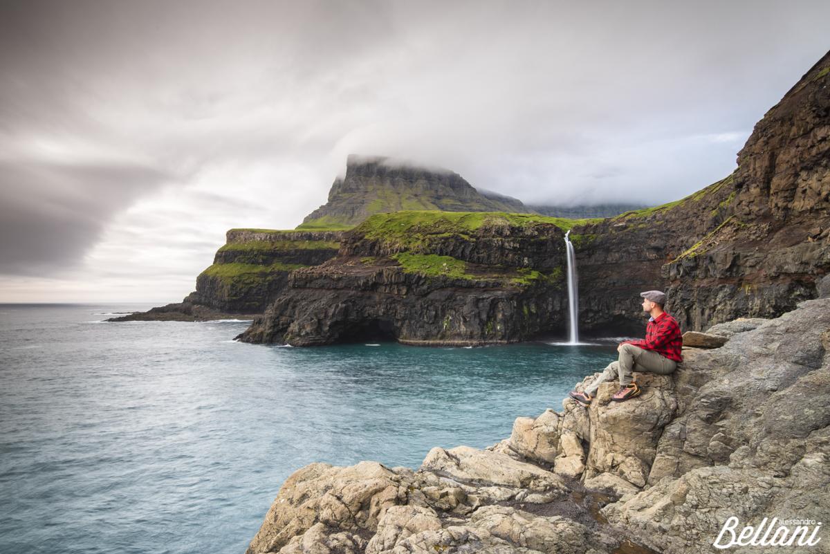 Hiker admiring the waterfall of Gasadalur FAROE ISLANDS